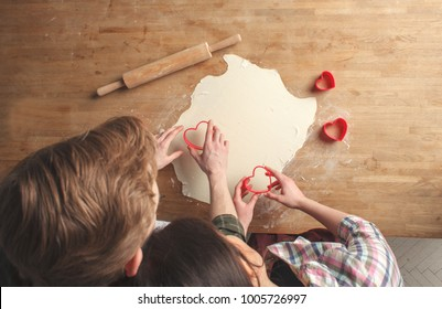 young lovely couple - boyfriend and girlfriend, making cookies in heart shape for Valentine's Day together, above view