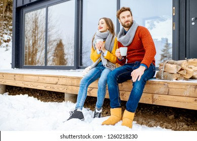 Young lovely couple dressed in colorful sweaters enjoying nature sitting together with hot drinks on the terrace of the modern house in the mountains