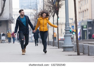 Young lovely couple having quality time together walking on city streets.