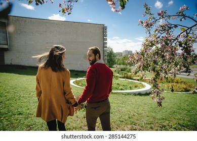 young lovely couple hipster family outdoors in park rear view