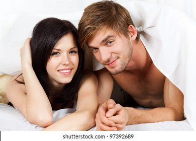 young lovely couple lying in a bed, happy smile looking at camera, cover under blanket