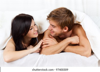 young lovely couple lying in a bed, happy smile looking to each other,  cover under blanket