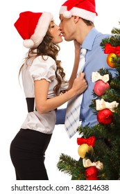 Young lovely couple near a Christmas tree. Isolated over white background