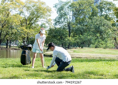 Young lovely couple playing golf together on a course near a lake, boyfriend teaching his girlfriend how to play golf. happy time in summer, concept of union and love