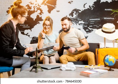 Young lovely couple sitting with manager at the travel agency office prepairing for a summer vacation