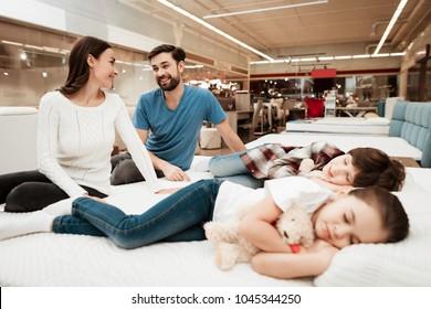 Le jeune couple est assis sur un matelas à côté d'enfants endormis dans un magasin de meubles. Tester la douceur du matelas. Choix du matelas en magasin