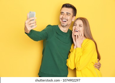 Young lovely couple taking selfie against color background