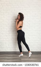 young and lovely fit woman posing on a brick wall bacground.