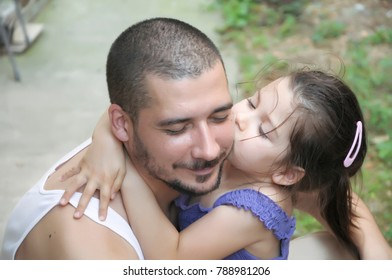 Young and lovely girl is hugging and kissing her father, while playing in the park.