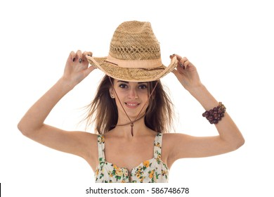 young lovely girl in sarafan with floral pattern and straw hat looking and smiling on camera isolated on white background