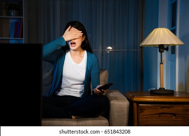 young lovely girl watching movie looking at terrible plot raised hand covering eyes and showing fear emotional sitting on living room sofa at night.