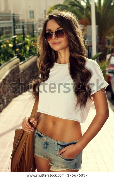 Young lovely tanned beautiful woman standing with handbag. Outdoor summer portrait of attractive girl in sunglasses