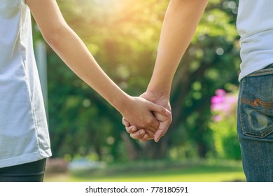 Young lover couple holding hands at green park outdoor, Romantic moments couple in love