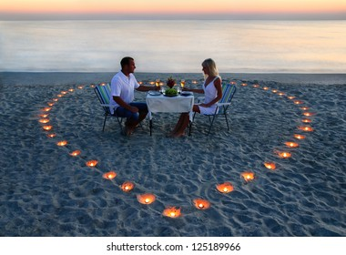 A young lovers couple share a romantic supper with candles heart on the sea beach