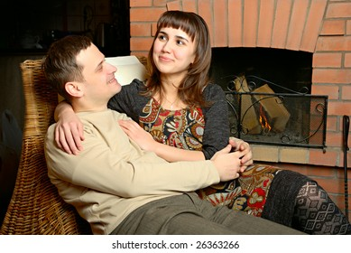 Young lovers - man and woman near fireplace
