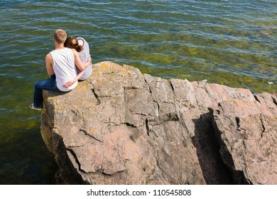 Young lovers sitting on the big rock on the shore