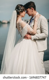 Young loving brides are walking, hugging, kissing in the city near blue lake in summer. Bride in boho style dress, man in beige suit. Wedding day, photo shoot, happiness, portrait. beautiful bouquet