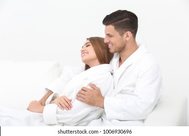 Young loving couple in bathrobes relaxing on sofa
