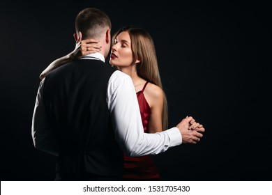 young loving couple dancing waltz. close up portrait, isolated black backgroud. studio shot, love, relation concept