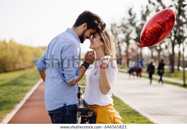 街で自転車に乗りながら付き合う若い恋人