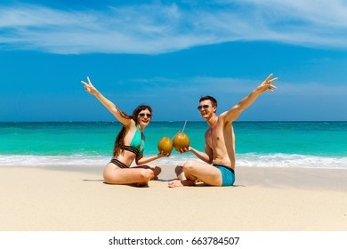 Young loving couple drink coconut on tropical beach. Summer vacation concept.