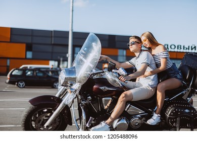 Young loving couple driving a bike in USA streets, happy and cheerful in summer vacation