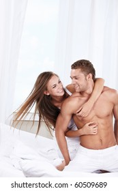 Young loving couple embrace in the bedroom