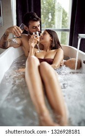 Young loving couple is enjoying a bath, embrace and kissing.
