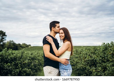 Young loving couple gently hugging on the background of green currant plantations. Love Story.