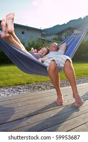 Young loving couple in a hammock in a summer setting. The woman is pregnant.