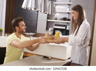 Young loving couple having breakfast together in the kitchen, both smiling, side view.