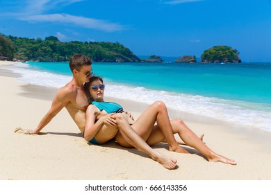 Young loving couple having fun on tropical beach. Summer vacation concept.