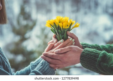 Young loving couple holding hands each other with bouquet of yellow flowers in summer park, view of hands