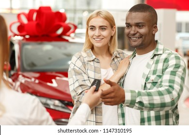 Young loving couple hugging while receiving keys to their new automobile from car seller. Handsome African man and his wife buying new car at the dealership. Auto dealer passing car key to customers