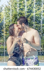 Young loving couple kisses and drink wine in the hydromassage of swimming pool. Concept of young people having fun in summertime