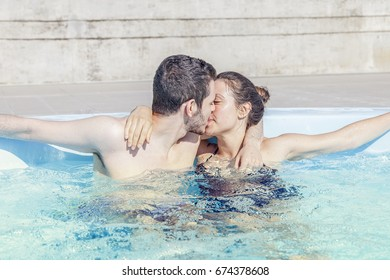 Young loving couple kisses and relaxes in the hydromassage of swimming pool. Concept of young people having fun in summertime