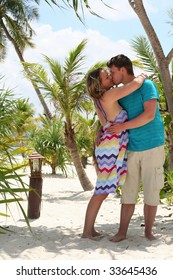 Young loving couple kissing on sand beach of tropic paradise