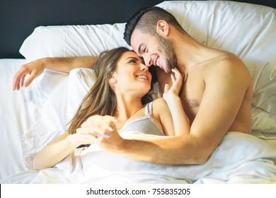 Young loving couple lying in bed cuddling looks each other under white blankets - Beautiful and happy lovers having tender and romantic moments in the bedroom - Relationship, intimate, love concept