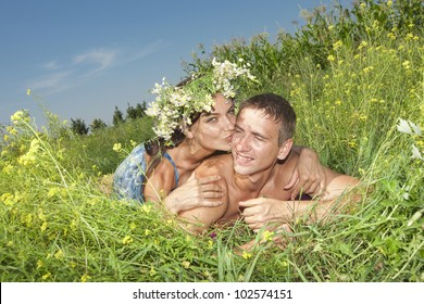Young loving couple lying on green grass