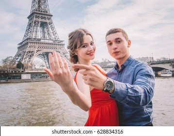 Young loving couple making proposal under Eiffel tower in Paris, France.