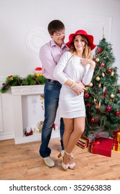 The young loving couple on Christmas, in the white room in the Christmas decor, full length.