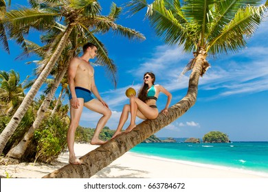 Young loving couple on a palm tree on a tropical beach. Tropical sky and sea in the background. Summer vacation concept.