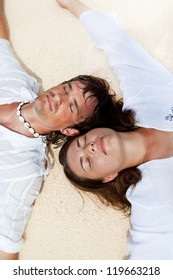 Young loving couple on sand, enjoying each other