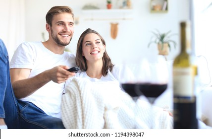 Young loving couple on sofa at home watching tv and laughing, drinking a glass of red wine.