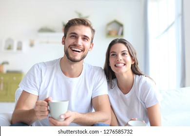 Young loving couple on sofa at home watching tv and laughing.