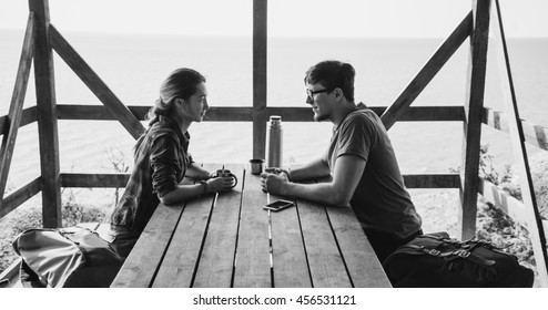 Young loving couple resting in wooden terrace and talking with each other in summer outdoor. Monochrome image