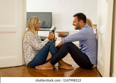 Young loving couple sitting on the floor with digital tablet in the room