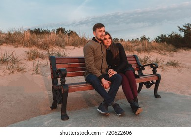 young loving couple sitting on benches near the sea shore in autumn.