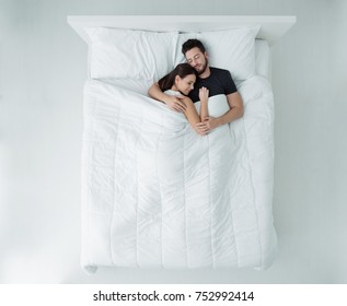 Young loving couple sleeping in bed, they are hugging, top view