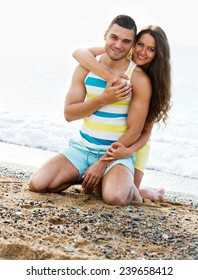 Young  loving couple spending free time at seaside in summer day